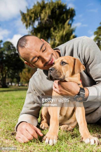 Young man laying on the grass while cuddling his puppy at the park.