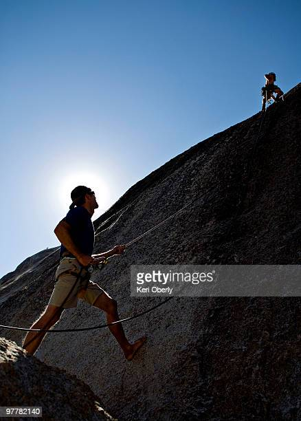 a young man leads a rock climb, while another young man belays him, in yosemite, california. - messa in sicurezza foto e immagini stock