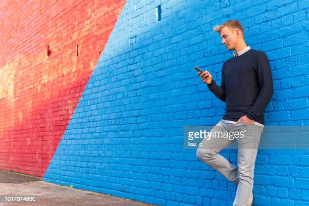 young man leaning against a brick wall while using a smart phone - bright blue background stock pictures, royalty-free photos & images