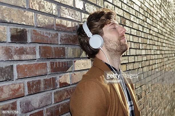 Young man leaning against brick wall listening music with headphones