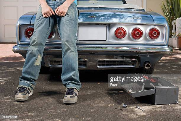 Young Man Leaning Against Car Trunk