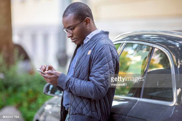 Young man leaning against car using cell phone