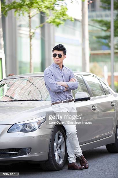 Young man leaning against his car