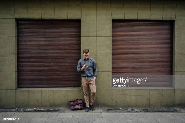 young man leaning against house front using cell phone - wachten stockfoto's en -beelden