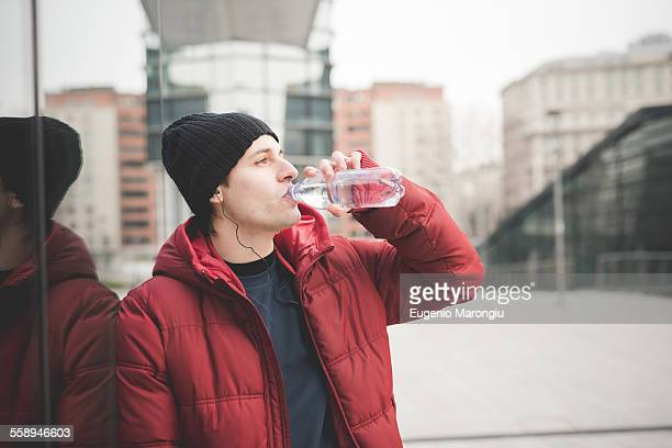 Young man leaning against office building drinking water