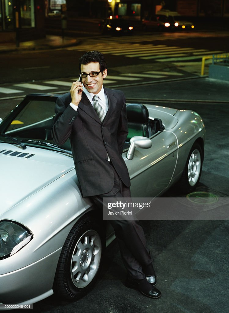 Young Man Leaning Against Sports Car, Talking On Cell Phone, Night : Stock  Photo