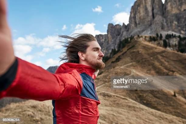 young man leaning against the wind in the mountains - windswept stock pictures, royalty-free photos & images