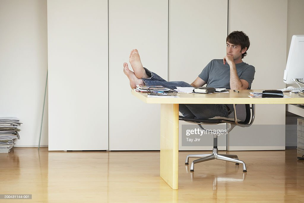 Jeune homme sappuyant en fauteuil les pieds au bureau pour