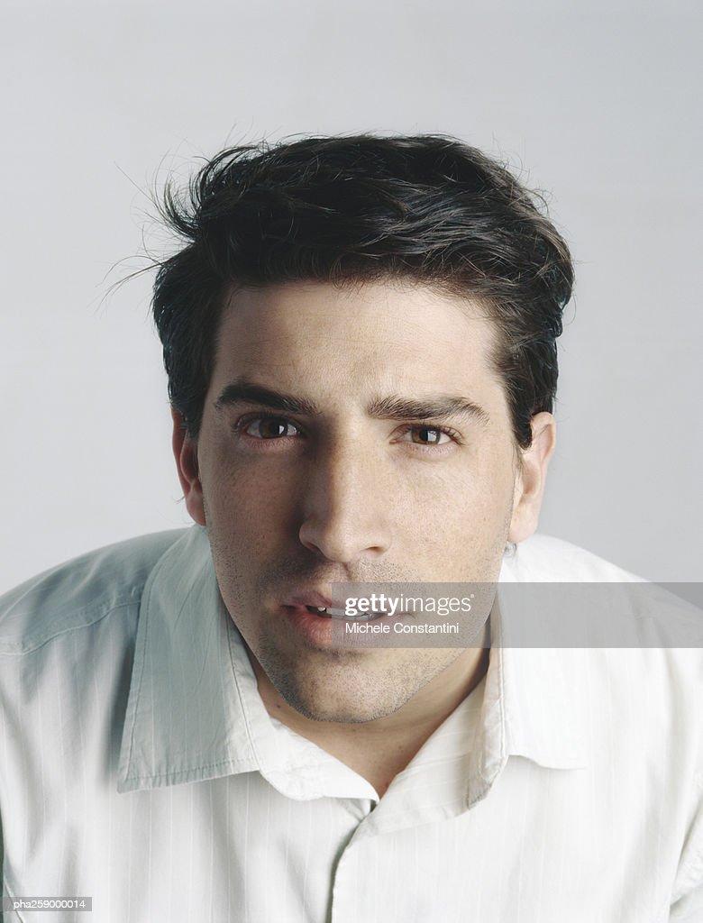 Young man leaning, looking at camera : Stockfoto