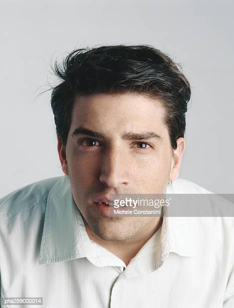 young man leaning, looking at camera - squinting stock photos and pictures