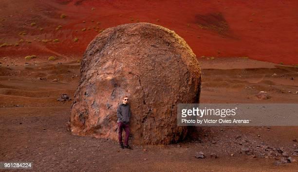 young man leaning on a huge volcanic block (pyroclastic rock) in caldera colorada volcano in lanzarote, canary islands, spain - victor ovies fotografías e imágenes de stock