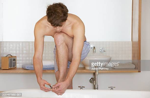 Young man leaning on bath cutting toenails