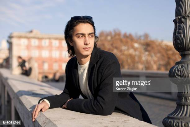 Young man leaning on bridge, Ponte Sisto, Rome, Italy