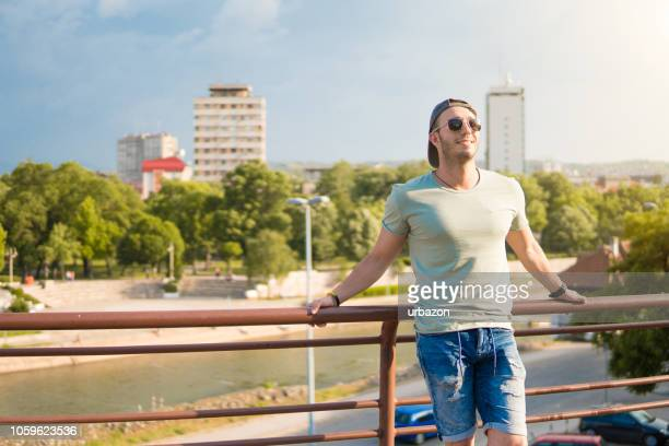 Young man leaning on fence