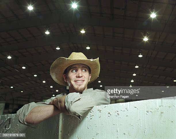 Young man leaning on gate in rodeo, looking to side, smiling