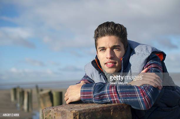 Young man leaning on groyne, Brean Sands, Somerset, England