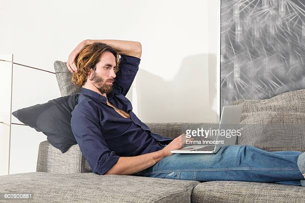 young man leaning on sofa with laptop - florence douillet photos et images de collection