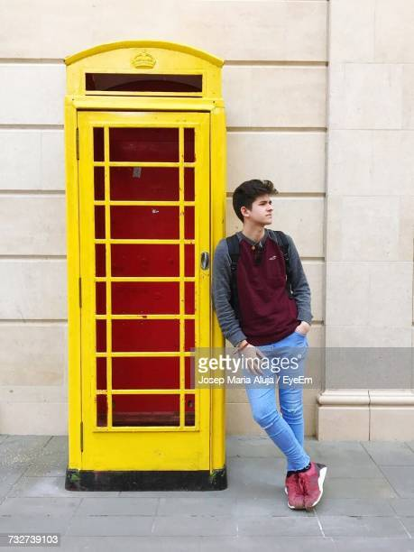Young Man Leaning On Telephone Booth On Footpath Against Building