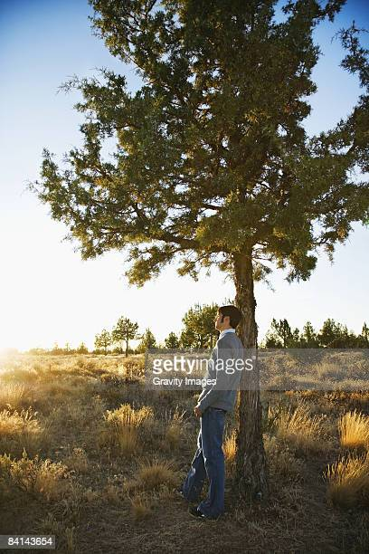 Young man leaning on tree