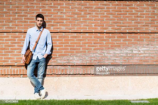 young man leaning on wall in the city - appoggiarsi foto e immagini stock