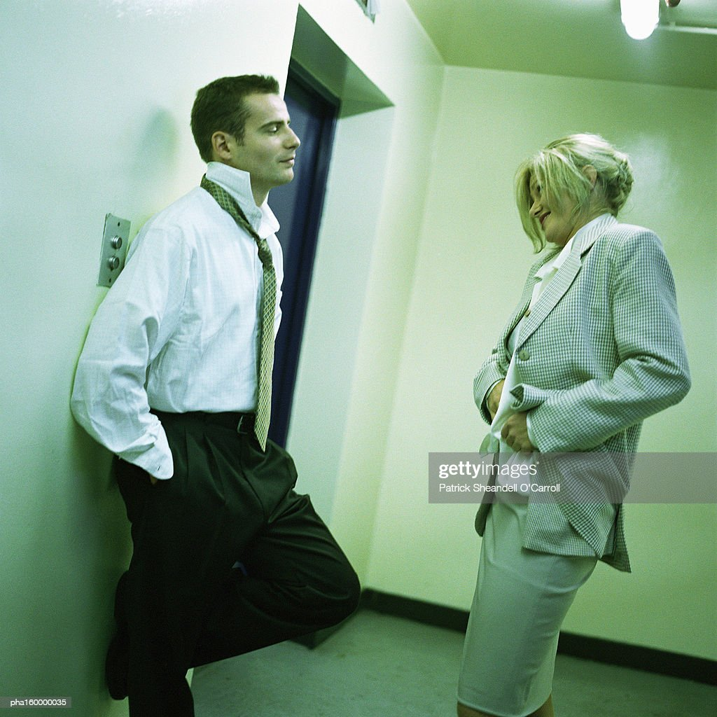 Young man leaning on wall, woman adjusting her clothing, side view. : Stockfoto