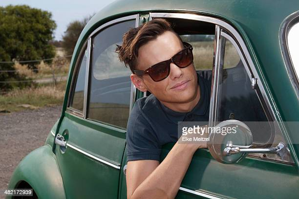 Young man leaning out of vintage morris minor