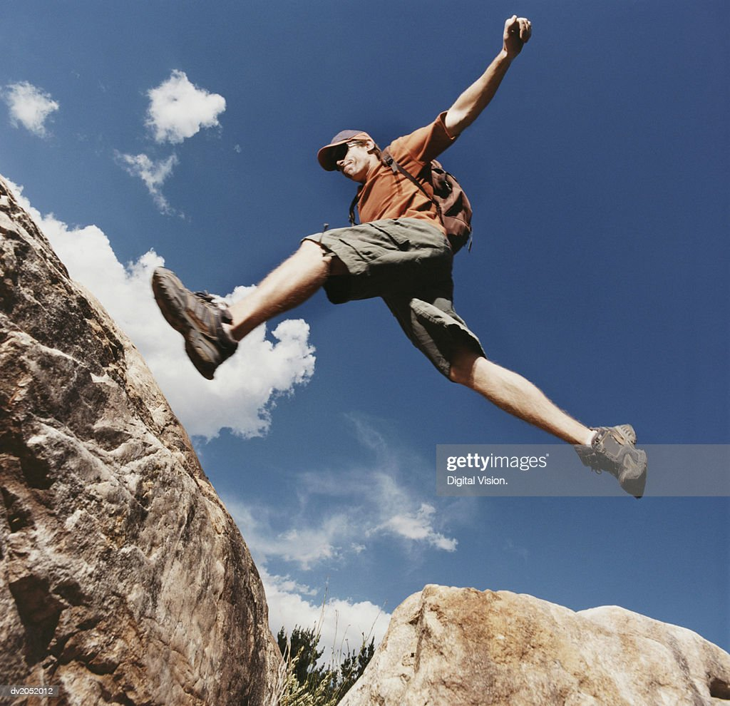 Young Man Leaping Between Rocks : Stock Photo