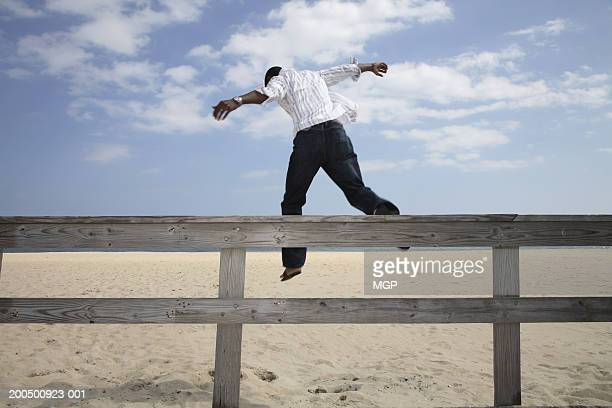 Young man leaping from fence onto beach, rear view
