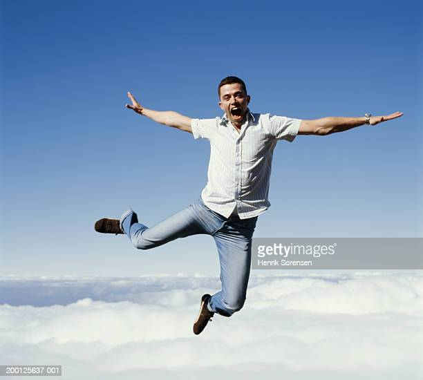 young man leaping in the air, clouds in background, portrait - short sleeved stock pictures, royalty-free photos & images