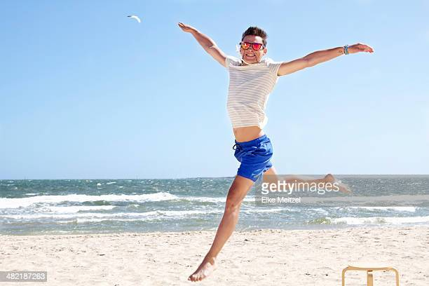 Young man leaping mid air on beach, Port Melbourne, Melbourne, Australia