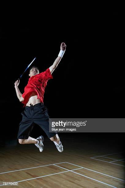 young man leaps high in the air and prepares to smash a shuttlecock during a game of badminton. - badminton smash stock pictures, royalty-free photos & images