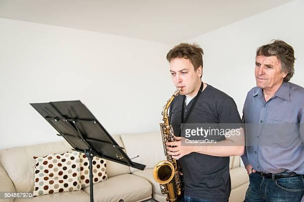 Junger Mann lernen, spielen Saxophon wie zu Hause fühlen.