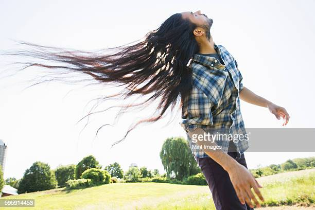 a young man letting down his very long dark hair and shaking his head to fan it out in the fresh air. - long hair stock pictures, royalty-free photos & images
