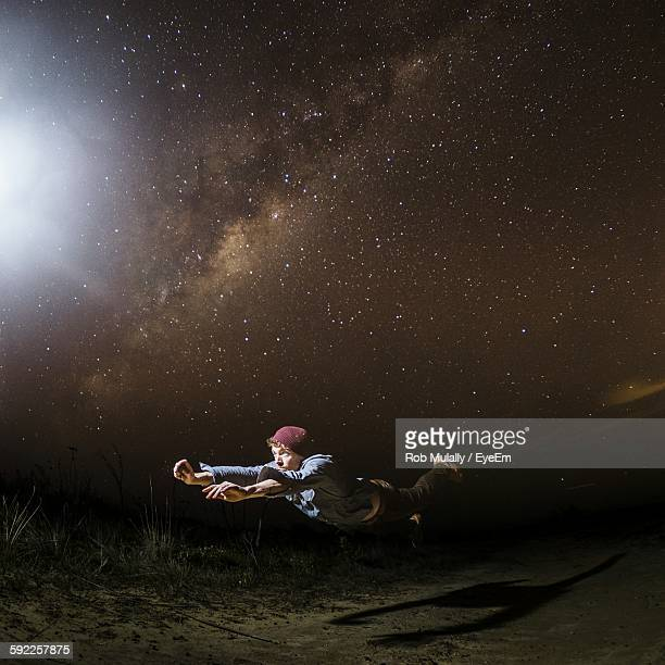 Young Man Levitating Above Field At Night