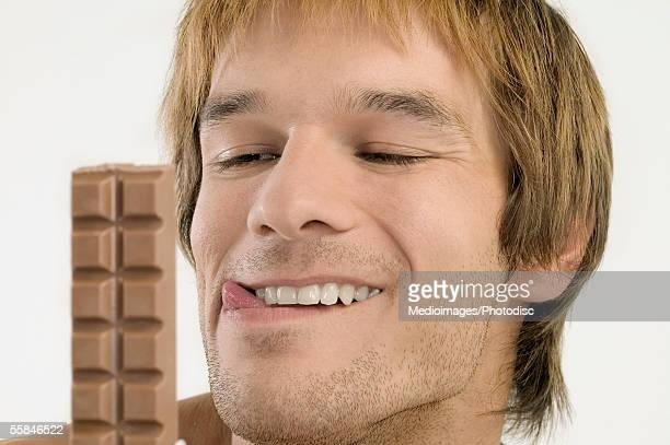 Young man licking his lips and looking at chocolate candy bar