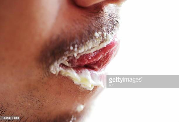 Young man licking with cream in mouth,close up