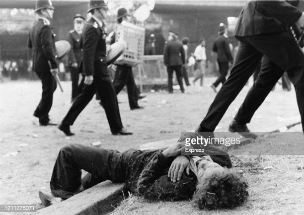 Young man lies after being injured during riots at the Notting Hill Carnival, London, UK, 31st August 1976.