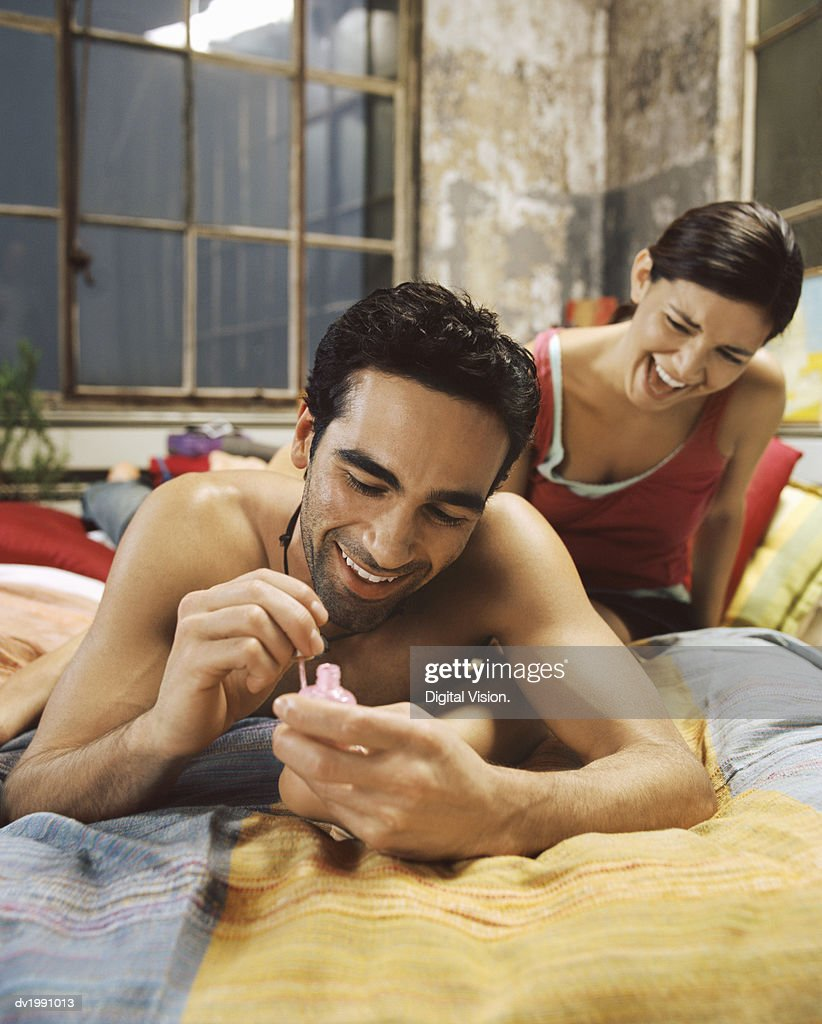Young Man Lies on a Bed, Painting His Girlfriend's Toenails : Stock Photo