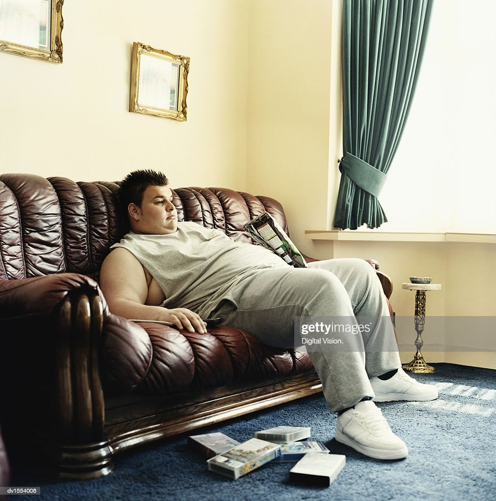 Young Man Lies Slouched on a Sofa Watching Videos and Holding a Packet of Crisps : Stock Photo