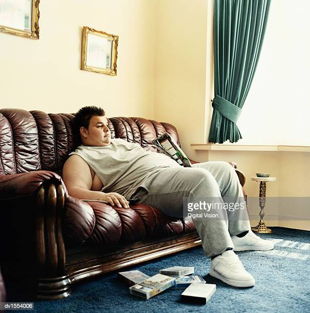 young man lies slouched on a sofa watching videos and holding a packet of crisps - gordo fotografías e imágenes de stock