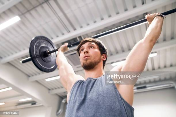 Young man lifting barbell