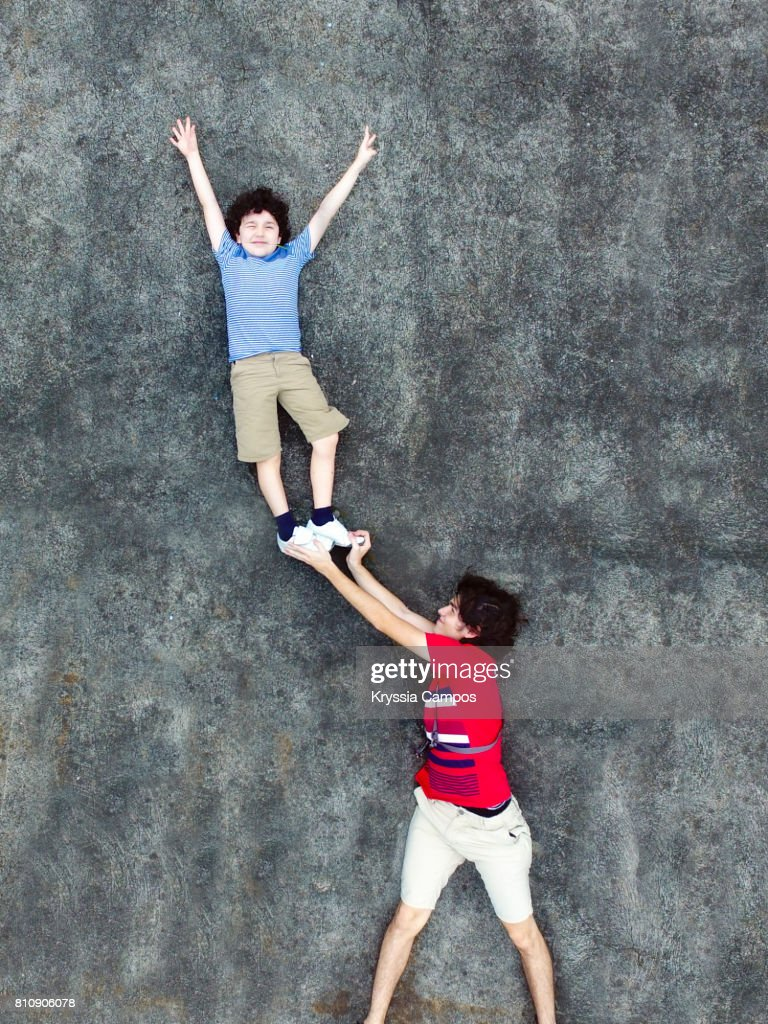 Young man lifting brother above head : Stock Photo