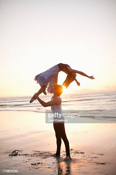 Young man lifting dancing partner on sunlit beach
