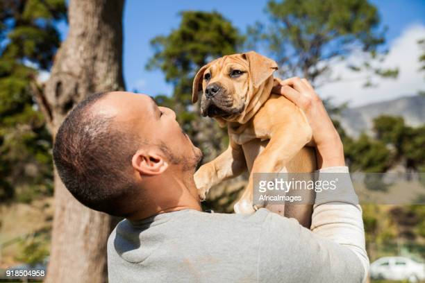 Young man lifting his dog in the air while playing at the park.