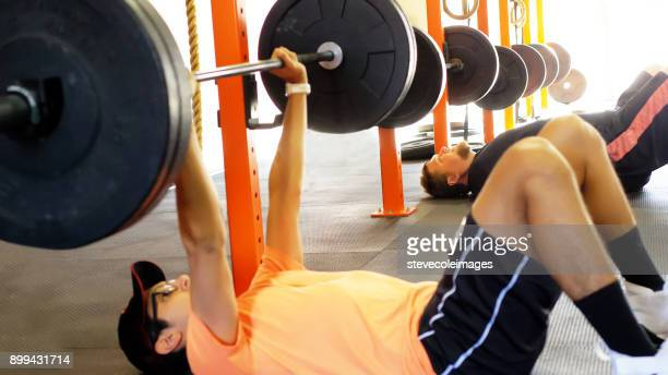 Young man lifting weight with barbell.