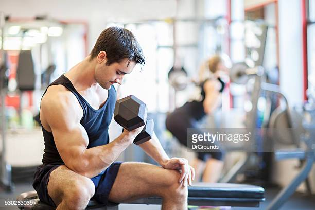 Junger Mann, Gewichtheben im Fitnessraum