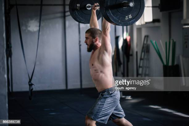 young man lifting weights - snatch weightlifting stock photos and pictures