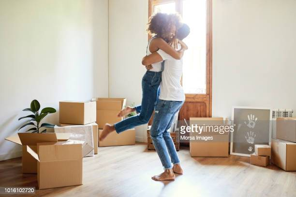 young man lifting woman in new house - home ownership stock pictures, royalty-free photos & images