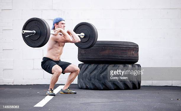 A young man lifts weights during a fitness boot camp.