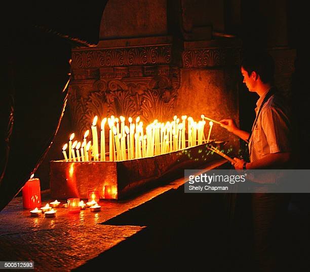 Young man lighting candles at the Church of the Holy Sepulchre in the ancient city of Jerusalem, Israel. The Church of the Holy Sepulchre, also...